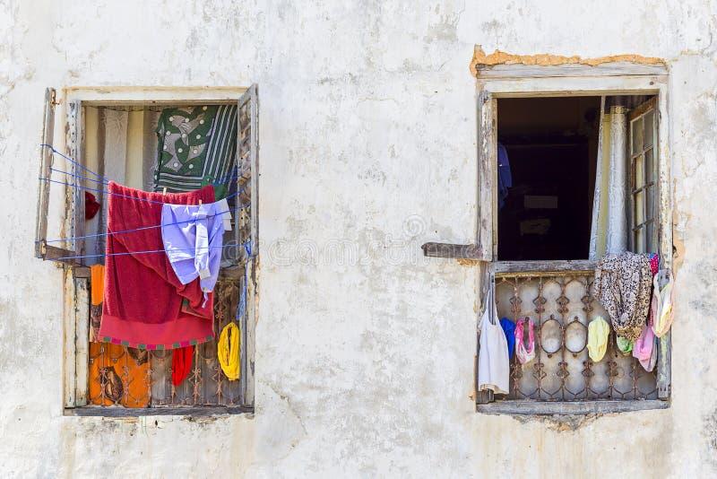 Twee vensters met kleren die op het raamkozijn en washline hangen stock afbeelding