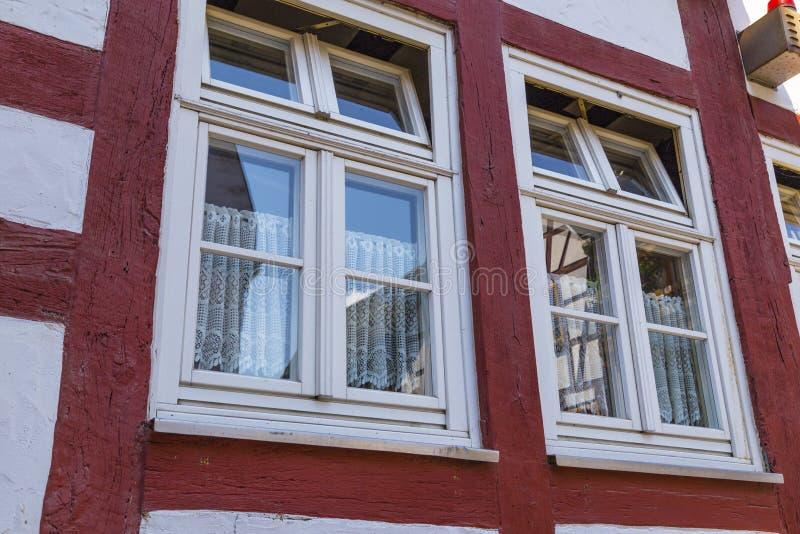 Twee vensters op de voorgevel van oud helft-betimmerd huis royalty-vrije stock afbeelding