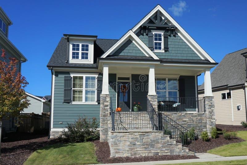 Twee-verhaal, huis in de voorsteden met een steenportiek in een buurt in Noord-Carolina stock afbeelding