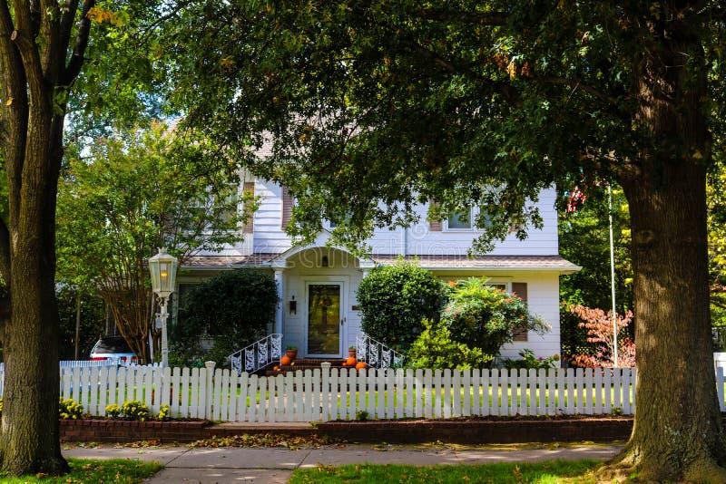 Twee verhaal wit houten huis met de pompoenen van de piketomheining en een Amerikaanse die vlag door twee grote bomen wordt gefla royalty-vrije stock afbeelding