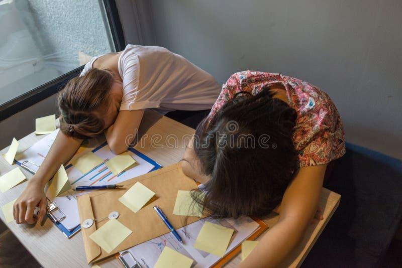 Twee vermoeid vrouwengezicht onderaan bureauhoogtepunt van kleverige nota's stock foto