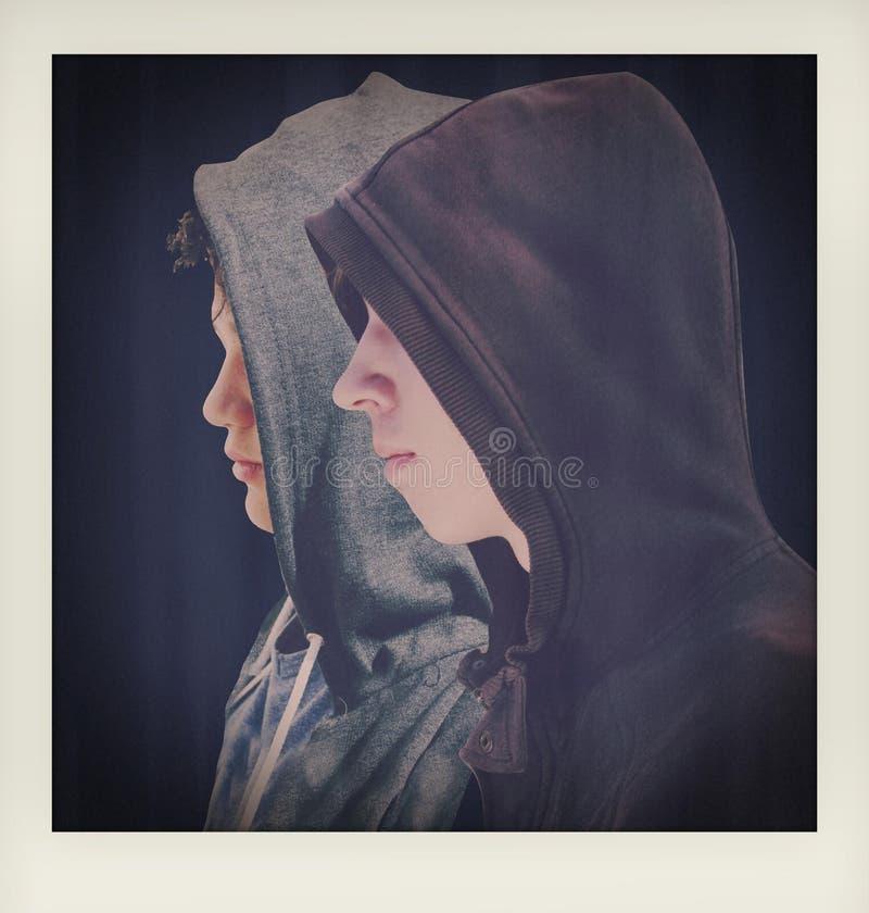 Twee verontruste tieners met zwarte hoodie die zich naast elkaar in profiel bevinden - gemaakt lige tot een onmiddellijke momento stock fotografie