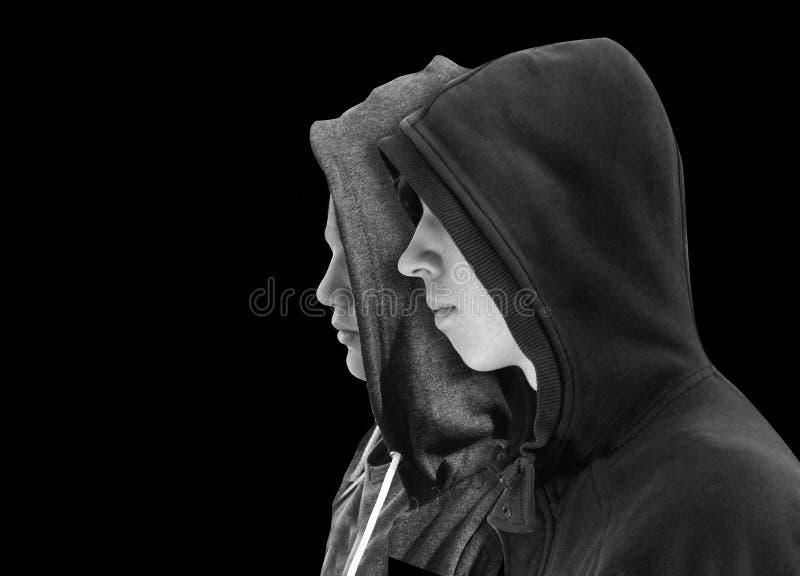 Twee verontrustten tieners met zwarte hoodie die zich naast die elkaar in profiel bevinden op zwarte achtergrond wordt geïsoleerd stock foto