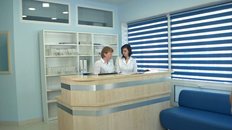Twee verpleegsters die bij ontvangstbureau werken die mannelijke patiënt begroeten stock fotografie