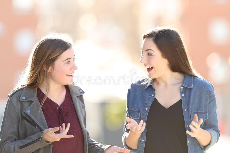 Twee verraste vrienden die in de straat spreken royalty-vrije stock foto's