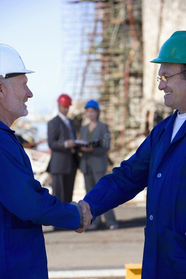 Twee verschepende ingenieurs die handen schudden stock fotografie