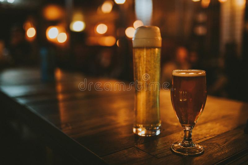 Twee verschillende bieren op een houten lijst stock foto's