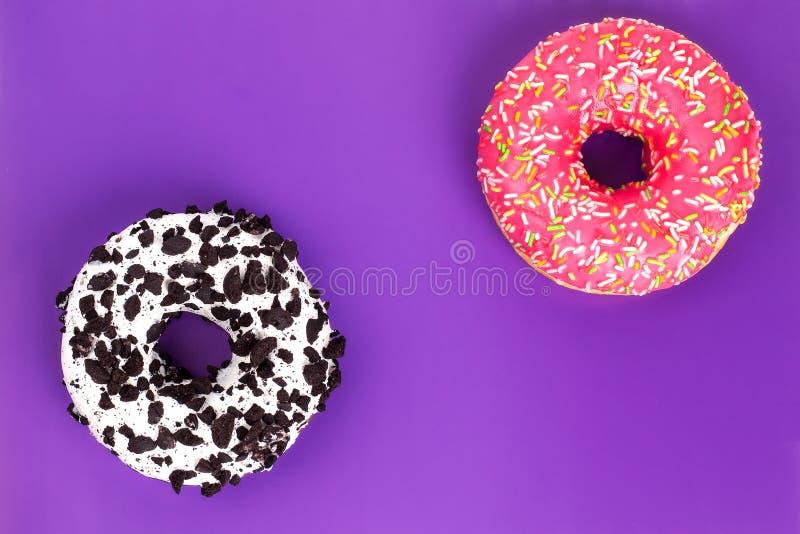 Twee verschillende donuts op purpere achtergrond royalty-vrije stock afbeeldingen