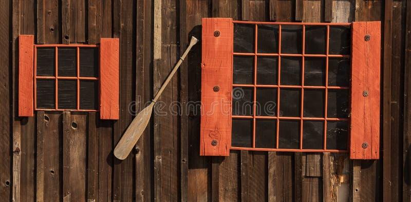 Twee verschillende grootte rode ontworpen vensters met bootpeddel op muur stock afbeelding