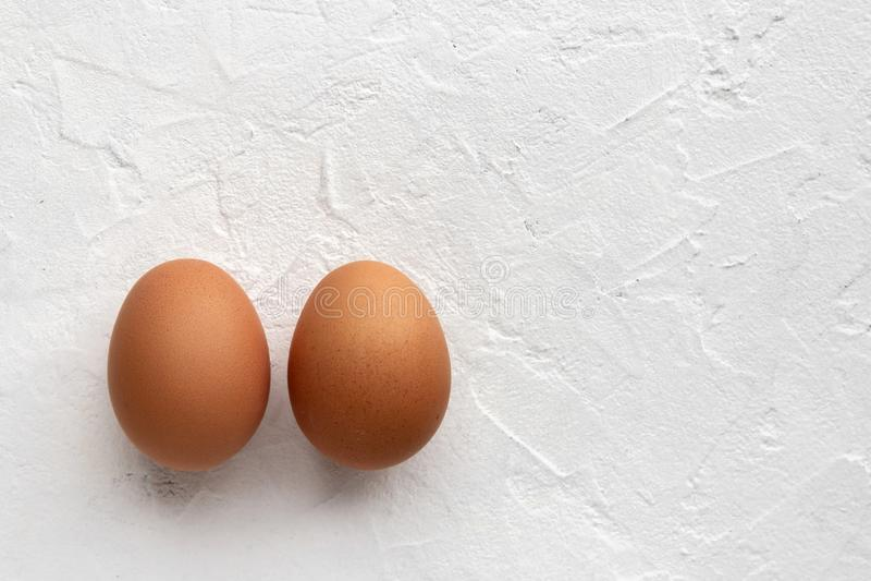 Twee verse eieren op witte weefselachtergrond met de schaduw van het ei stock afbeelding
