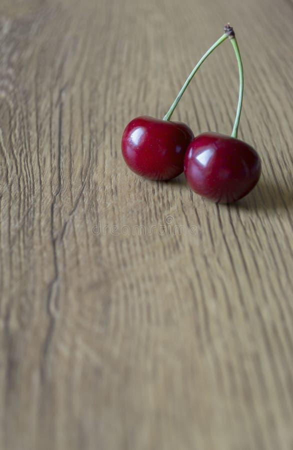 Twee verse kersen op houten achtergrond stock foto