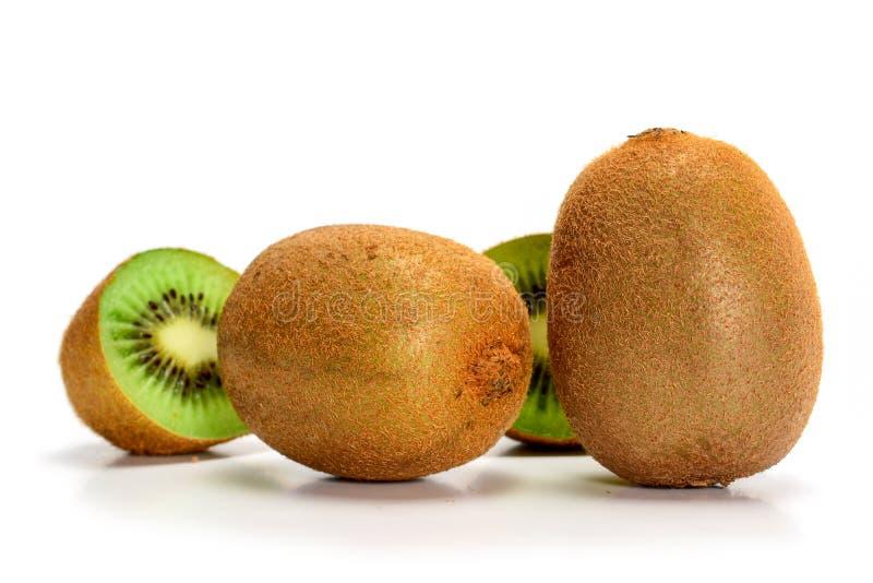 Twee verse, rijpe hele kiwi-vruchten en twee helften, geïsoleerd op witte achtergrond met schaduwen, afsluitend stock foto