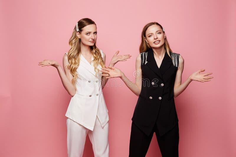 Twee verwarde vrouwelijke tweelingen in witte en zwarte in kostuums stock afbeeldingen