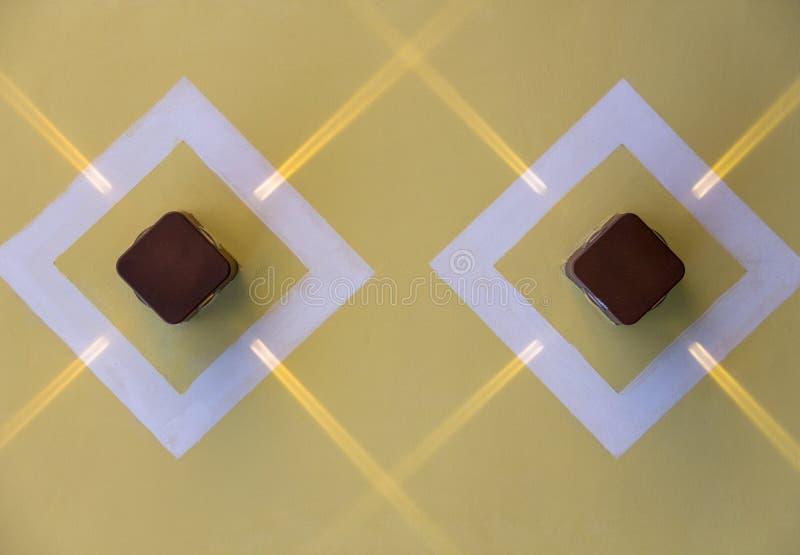 Twee vierkante bruine lampen met stralen van licht op een gele muur in witte ruiten Ruwe Oppervlaktetextuur stock foto