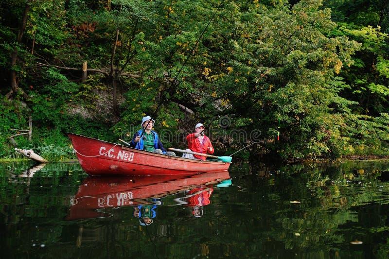 Twee vissers in een boot met hengels die vissen vangen stock afbeelding