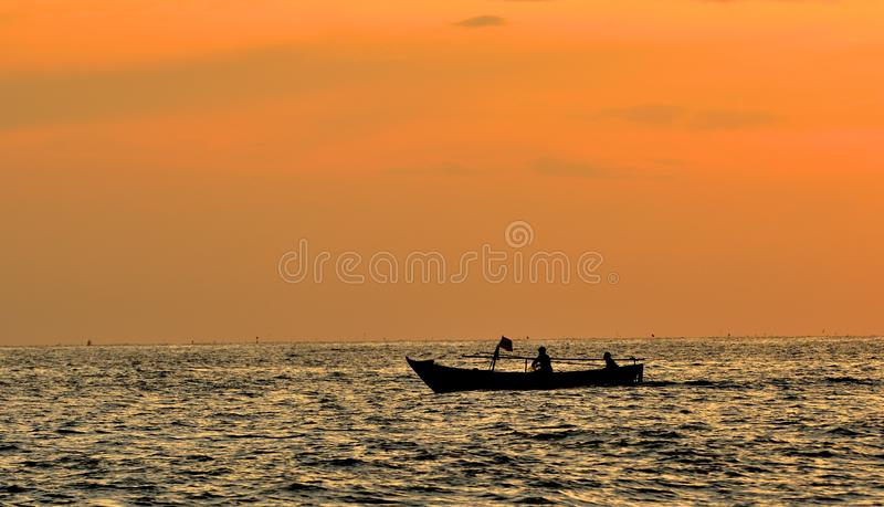 Twee vissers nemen een kleine vissersboot aan het overzees bij zonsondergang stock foto