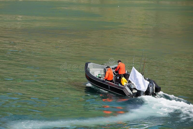 Twee vissers varen op een motorboot met een vlag op het water stock fotografie