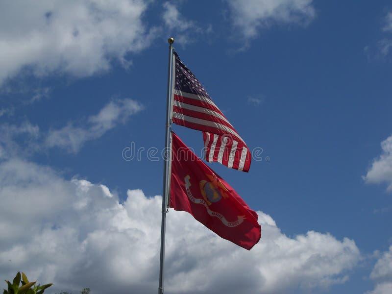 Twee vlaggen tegen een blauwe gedeeltelijk bewolkte hemelslag in de wind stock foto's