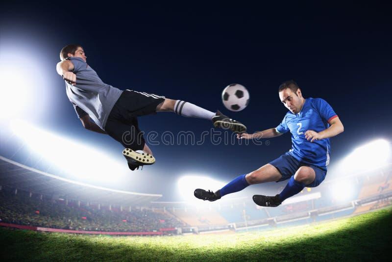 Twee voetballers die in medio lucht de voetbalbal, stadionlichten bij nacht op achtergrond schoppen stock afbeeldingen