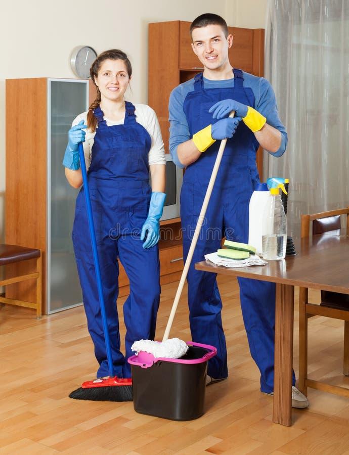Twee volwassen reinigingsmachines die vloer schoonmaken stock foto