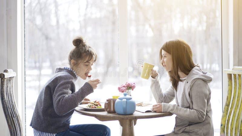Twee volwassen vrouwelijke vrienden die en thee in een koffie eten drinken royalty-vrije stock afbeelding
