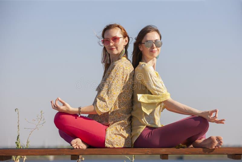 Twee volwassen vrouwen verouderde yoga in openlucht in de zomer in het park royalty-vrije stock fotografie