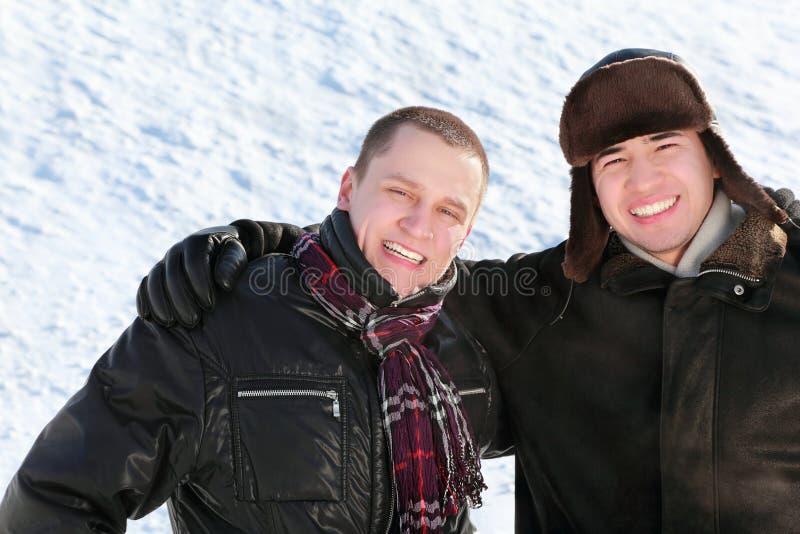 Twee vrienden bevinden zich op sneeuw in greep en glimlach royalty-vrije stock foto's