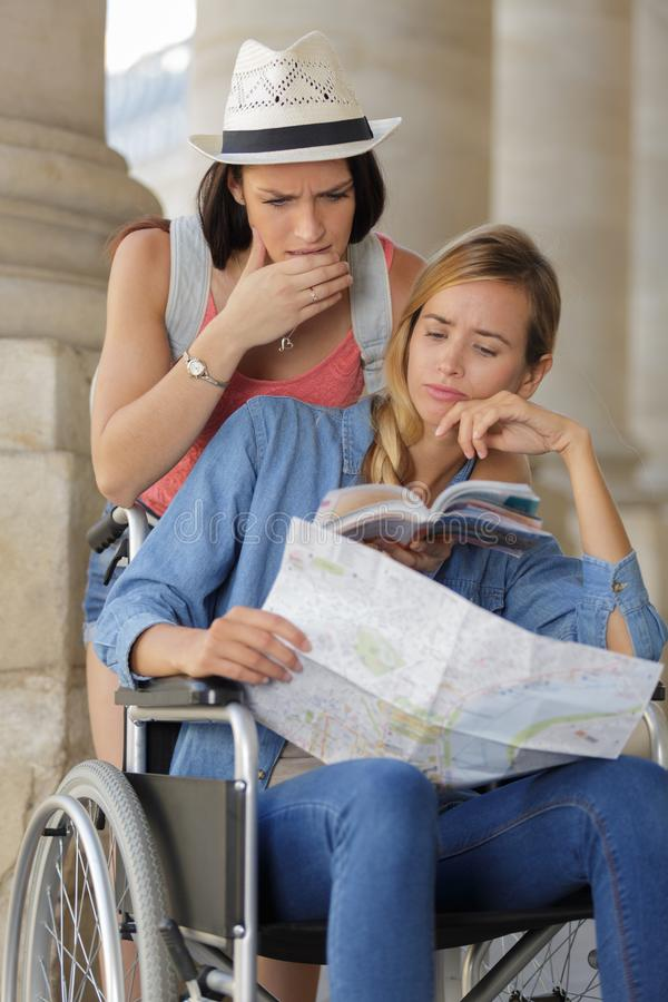 Twee vrienden die buitenlandse stad één bezoeken zitting in rolstoel royalty-vrije stock foto's