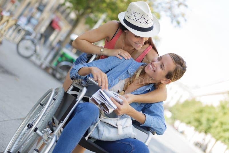 Twee vrienden die buitenlandse stad één bezoeken zitting in rolstoel stock afbeeldingen