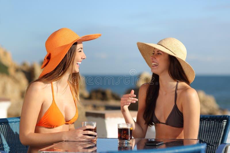 Twee vrienden die in een hotel op vakantie spreken royalty-vrije stock fotografie