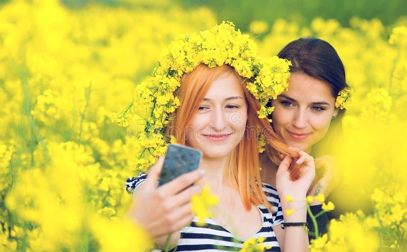 Twee vrienden die een selfie op een gebied met gele bloemen van raapzaad nemen stock foto