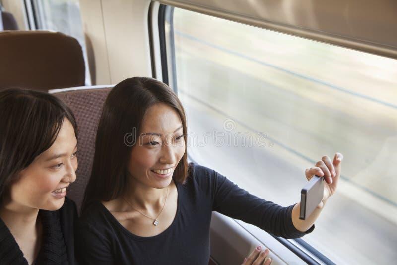 Twee Vrienden die en een Beeld glimlachen nemen het Treinvenster stock foto's