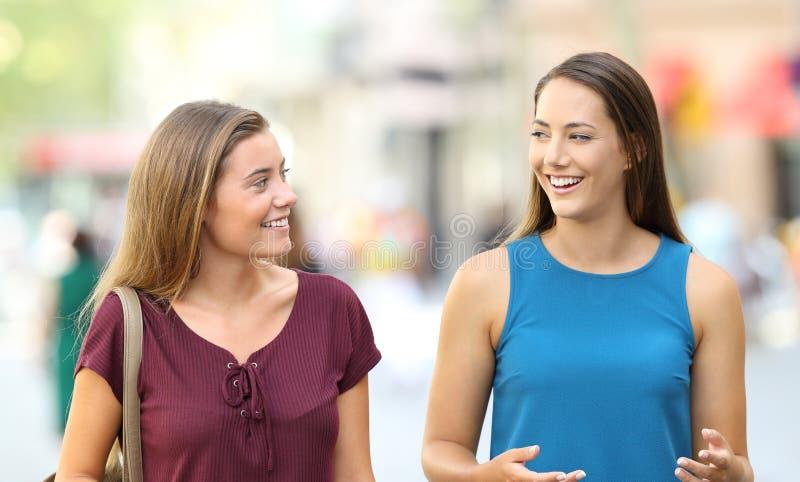 Twee vrienden die en op de straat lopen spreken royalty-vrije stock afbeeldingen