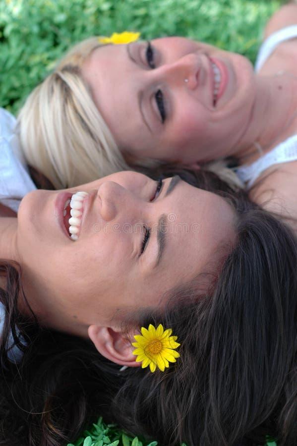 Twee vrienden die in gr. ontspannen stock afbeeldingen