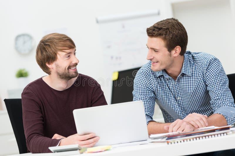Twee vrienden die in het bureau samenwerken royalty-vrije stock afbeelding