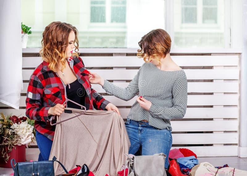 Twee vrienden die kleren van haar garderobe kiezen Het concept fas royalty-vrije stock foto's