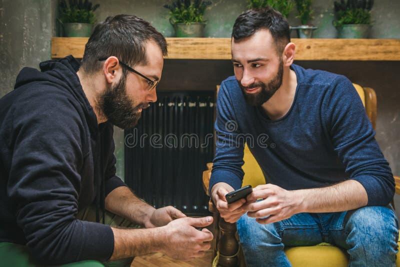 Twee vrienden die media op inhoud in een slimme telefoon letten stock foto