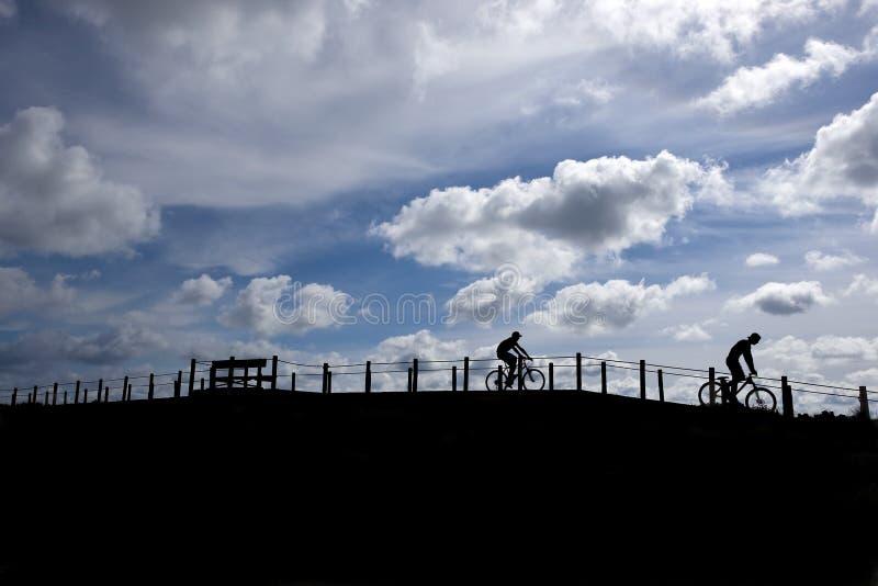 Twee vrienden die moutain fietsen berijden stock foto's