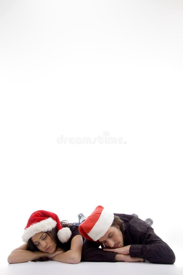 Twee vrienden die op de vloer met Kerstmishoed liggen stock foto