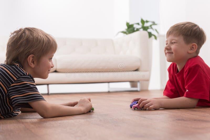 Twee vrienden die op vloer thuis spelen stock fotografie