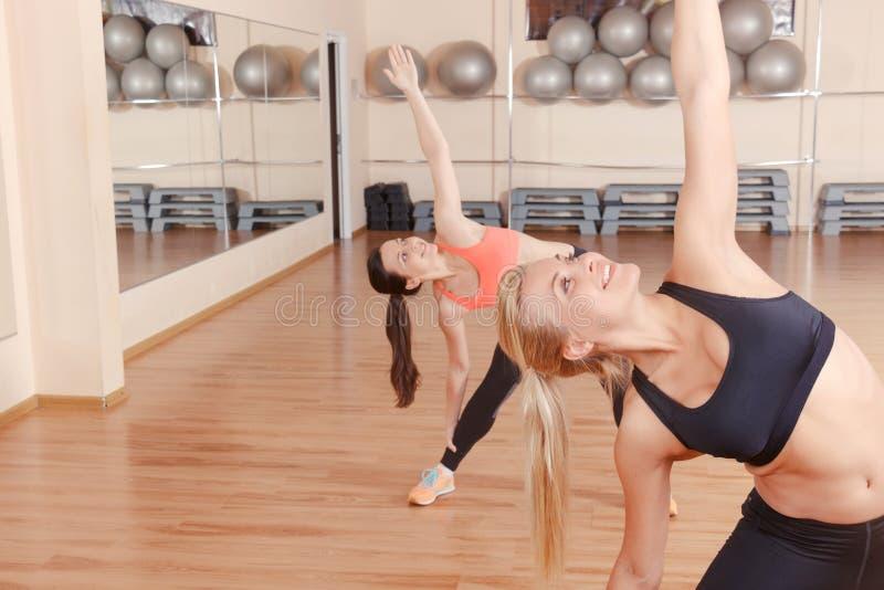 Twee vrienden die uitrekkende oefeningen in gymnastiek doen royalty-vrije stock fotografie