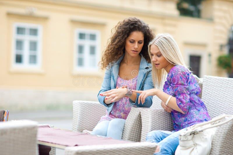Twee vrienden die van de tienervrouw pret in openluchtkoffie hebben royalty-vrije stock fotografie