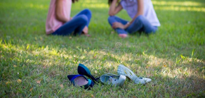 Twee vrienden die van het tienermeisje op gras situeren royalty-vrije stock foto