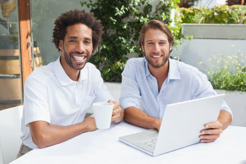 Twee vrienden die van koffie samen met laptop genieten royalty-vrije stock fotografie