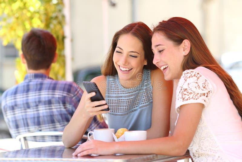 Twee vrienden of familie die een slimme telefoon in een koffiewinkel delen royalty-vrije stock foto