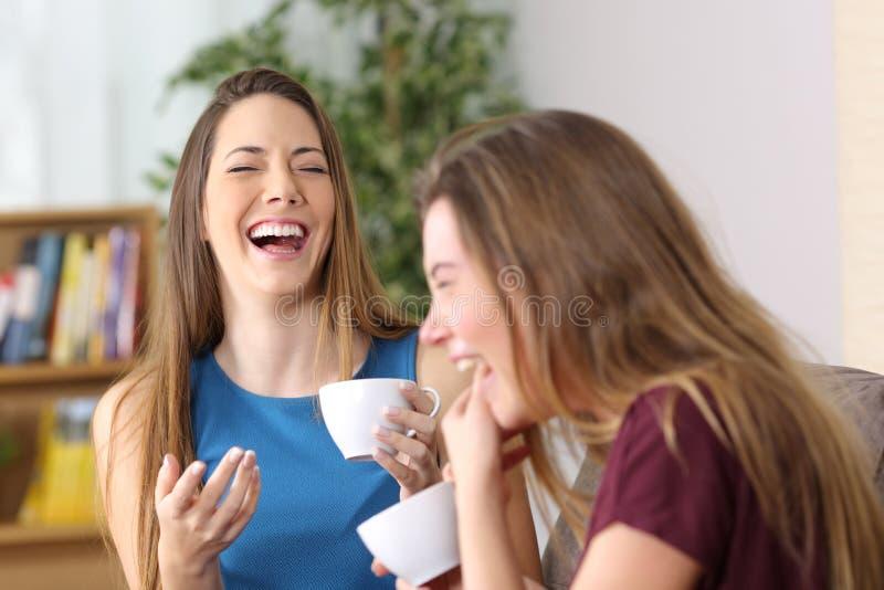Twee vrienden luid lachen thuis stock afbeeldingen