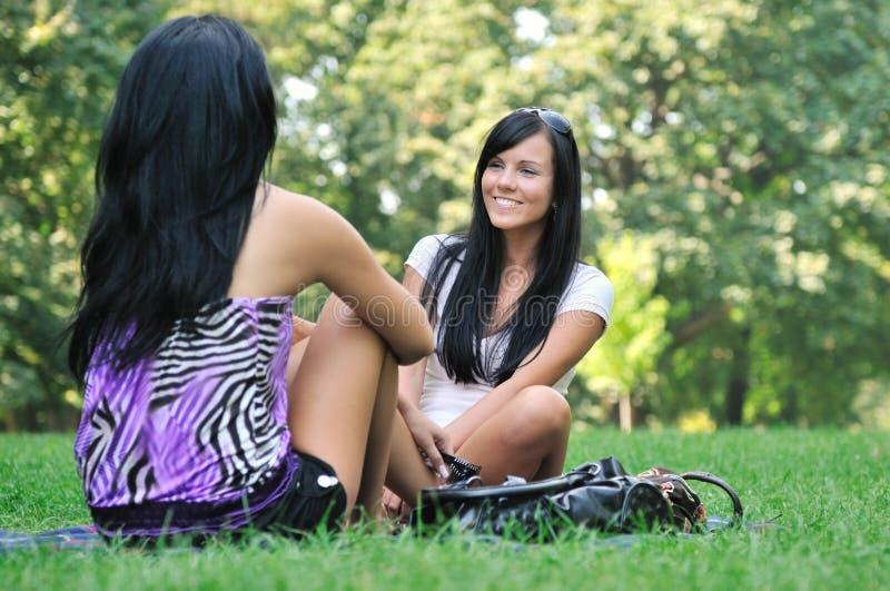 Twee vrienden - meisjes die buiten in park spreken stock afbeeldingen