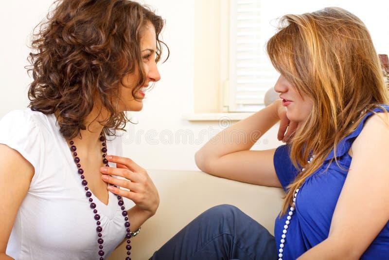 Twee vrienden op een laag die en pret heeft lacht stock afbeelding
