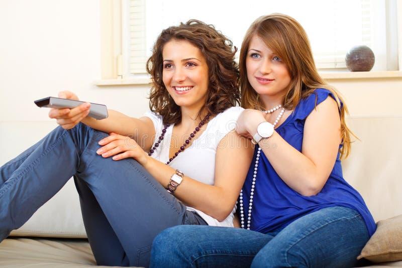 Twee vrienden op een laag die op TV let royalty-vrije stock afbeeldingen