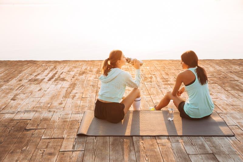 Twee vrienden van sportenvrouwen in openlucht op de strandzitting die met elkaar spreken stock afbeeldingen